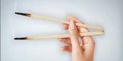 picture of hand with two burning chop stick